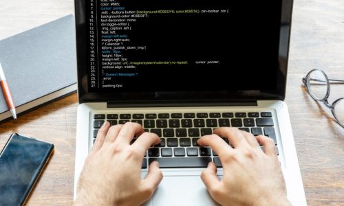Computer code, software concept. Programmer working with a laptop, programming code on the screen, office background. Developing coding technologies.