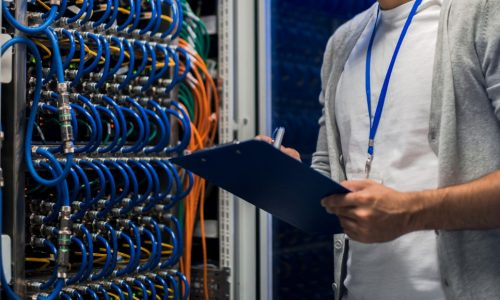 Portrait of young network engineer standing by server cabinet while working with supercomputer in data center and holding clipboard